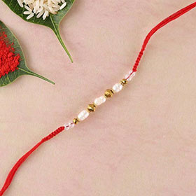 Freshwater pearls,brass beads and crystal in red flat woven rakhi thread