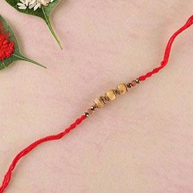 Sandalwood and brass bead rakhi in red thread